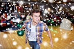 Bola que lanza feliz del hombre joven en club de los bolos Imagen de archivo libre de regalías