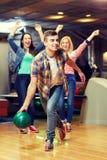 Bola que lanza feliz del hombre joven en club de los bolos Foto de archivo libre de regalías
