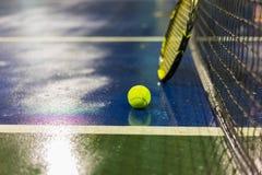 Bola, raquete e rede de tênis na terra molhada após chover Fotografia de Stock