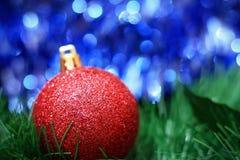 Bola roja de la decoración de la Navidad con el bokeh azul Fotografía de archivo