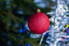 Bola roja de la decoración que cuelga en el árbol de navidad Fotos de archivo