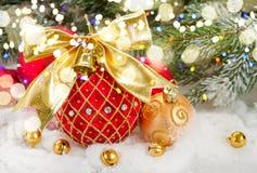 Bola roja de la Navidad con el arco de oro en nieve Fotografía de archivo