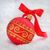 Bola roja de la Navidad con la cinta en la nieve Fotografía de archivo libre de regalías
