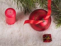Bola roja de la Navidad con las cajas de la cinta, de la vela y de regalo Imagen de archivo