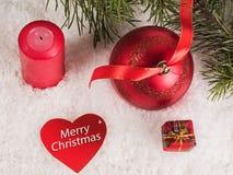 Bola roja de la Navidad con las cajas de la cinta, de la vela y de regalo Fotos de archivo libres de regalías