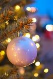 Bola roja de la Navidad con las luces de la guirnalda Foto de archivo