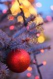 Bola roja de la Navidad con las luces de la guirnalda Imágenes de archivo libres de regalías