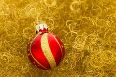 Bola roja de la Navidad en brillo del oro Fotografía de archivo libre de regalías