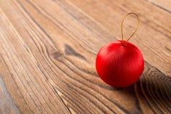 Bola roja de la Navidad en el fondo de madera Imagen de archivo libre de regalías