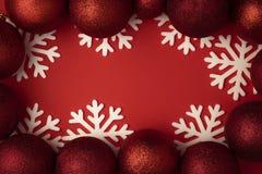 Bola roja de la Navidad en endecha plana del fondo rojo Decoración del invierno de la Navidad con el copo de nieve foto de archivo