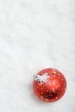 Bola roja de la Navidad en fondo nevoso Imagen de archivo libre de regalías