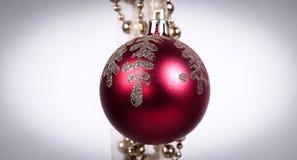 Bola roja de la Navidad y guirnalda de oro en el fondo blanco Fotografía de archivo