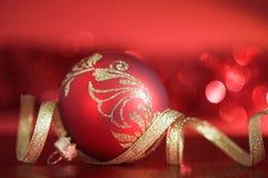 Bola roja de Navidad con la cinta de oro en fondo rojo Imagenes de archivo