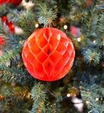 Bola roja de papel en el árbol de navidad Imagen de archivo libre de regalías