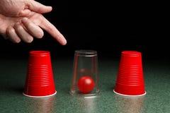 Bola roja debajo de la taza clara con la mano Imagen de archivo