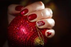 Bola roja del Año Nuevo y clavos brillantes en tono Fotografía de archivo libre de regalías
