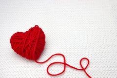 Bola roja del hilado como un corazón en el fondo blanco del ganchillo Concepto romántico del día de tarjetas del día de San Valen Fotos de archivo