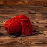 Bola roja del hilado y de las agujas que hacen punto con hacer punto en fondo de madera imágenes de archivo libres de regalías