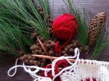 Bola roja del hilado y trabajo que hace punto el tiempo de la Navidad Imagen de archivo