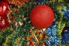 Bola roja en decoraciones brillantes y agujas verdes Fotografía de archivo