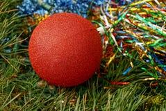 Bola roja en decoraciones brillantes y agujas verdes Fotografía de archivo libre de regalías