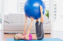 Bola rubia del ejercicio del ajuste que se sostiene alegre entre las piernas Fotos de archivo