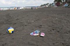 Bola, sandalia colorida y vidrios que nadan en la playa Foto borrosa de la gente en la playa de la arena Viaje o concepto de las  imagen de archivo