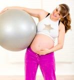 Bola sonriente de la aptitud de la explotación agrícola de la mujer embarazada Foto de archivo