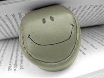 Bola sonriente de la cara en libro Foto de archivo