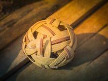 A bola velha do rattan (takraw do sepak) na madeira Foto de Stock