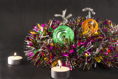 Bola verde y anaranjada grande de Navidad con la vela en la malla Imagen de archivo libre de regalías