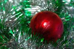 Bola vermelha da decoração do Natal com festão verde Foto de Stock Royalty Free