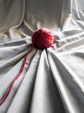 Bola vermelha de lãs com tela cinzenta foto de stock royalty free