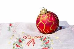 A bola vermelha do Natal bordou o guardanapo isolado imagens de stock