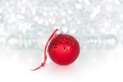 Bola vermelha do Natal na fita vermelha no fundo do ouropel brilhante, do bokeh branco das cápsulas, das luzes e dos sparkles pró imagem de stock