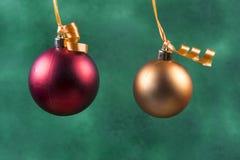 bola vermelha do Natal que pendura com a fita alaranjada no fundo verde imagens de stock royalty free