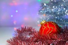 Bola vermelha do Natal sob a árvore e o ouropel fotografia de stock