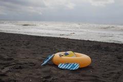 Bola, vidrios que nadan, sandalia, y anillo flotante en la playa En las vacaciones de verano imagen de archivo libre de regalías