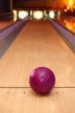 Bola violeta de la esfera que se coloca en carril largo del bowling imagenes de archivo