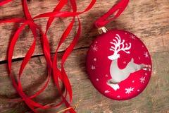 Bola y cintas rojas de la Navidad en fondo de madera Invitación del Año Nuevo Capítulo Visión superior Imagen de archivo libre de regalías