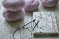 Bola y cuaderno de las lanas en la tabla Imagen de archivo libre de regalías