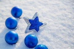 Bola y estrella azules de la Navidad en la nieve en un día soleado Foto de archivo libre de regalías