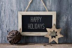 Bola y estrella de la Navidad, y texto buenas fiestas Fotografía de archivo libre de regalías