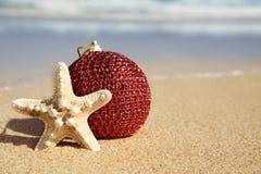 Bola y estrellas de mar de la Navidad en la arena de una playa Imágenes de archivo libres de regalías
