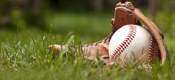 Bola y guante del béisbol en hierba verde Imagen de archivo