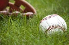 Bola y guante del béisbol en hierba verde Fotografía de archivo
