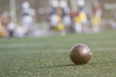 Bola y jugadores del fútbol americano en el fondo Imagen de archivo
