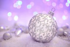 Bola y nieve de plata en Navidad Bokeh de la guirnalda púrpura Imagen de archivo