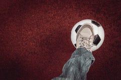 Bola y pie de fútbol en un rojo imagen de archivo