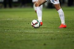 Bola y pies de un jugador de fútbol Imagenes de archivo